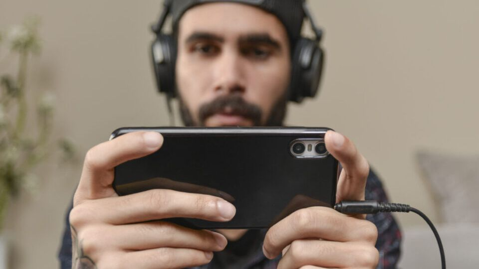 Young man paying a mobile game at home. Smart phone gaming